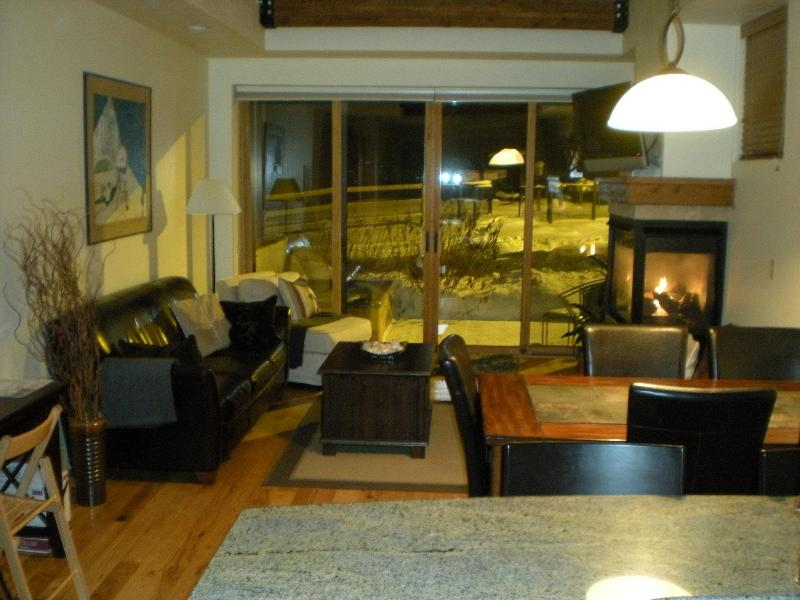 View from the kitchen looking at the dining table and living area with fireplace. - Park City Condo at Newpark: Great Location & Views - Park City - rentals