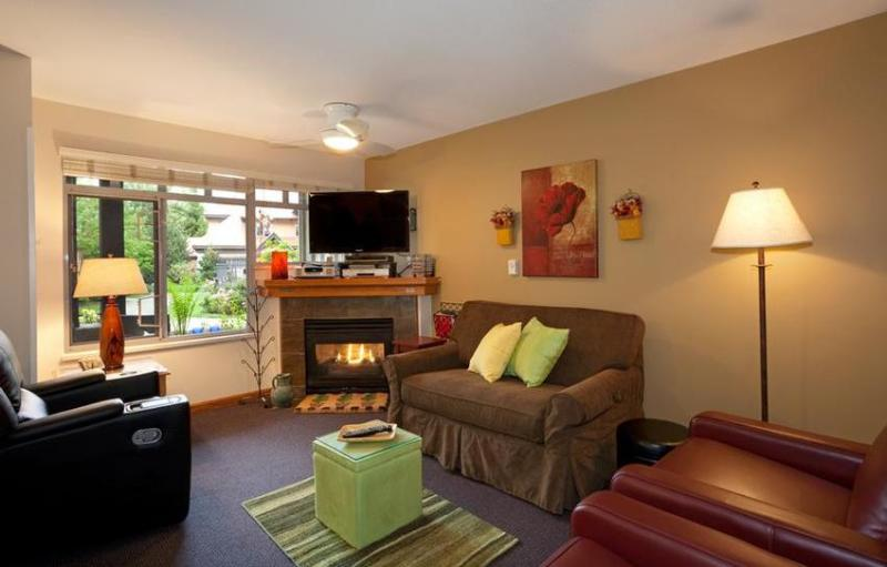 Spring view of living room with comfortable furniture, gas fireplace. View of front patio, pool area and view of mountains. - Sunpath's Well Equipped Condo - Whistler - rentals