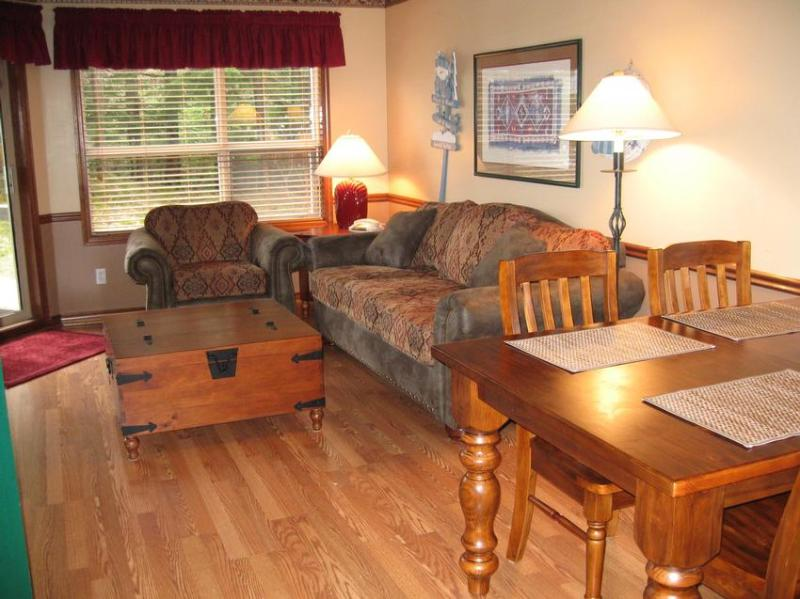 Living room with all new overstuffed furniture and a trunk coffee table. Slider to deck that overlooks the ski slope. Sofa is a sleeper bed with a built in air mattress, so it is very comfortable. This suite faces directly into the trees at the edge of the forest, but when you are sitting on the couch you have wonderful view of mountains and ski slope. - Judie and Eugene Herrera - Whistler - rentals
