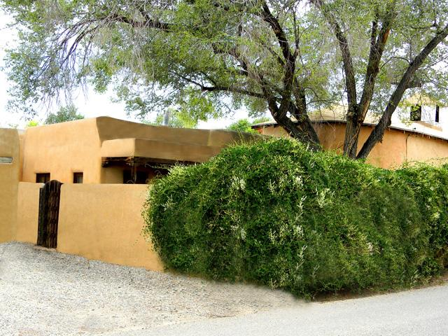 Front exterior with lush green flowering vines showing adobe walled enclosed private front yard - Casa Bonita - Taos - rentals