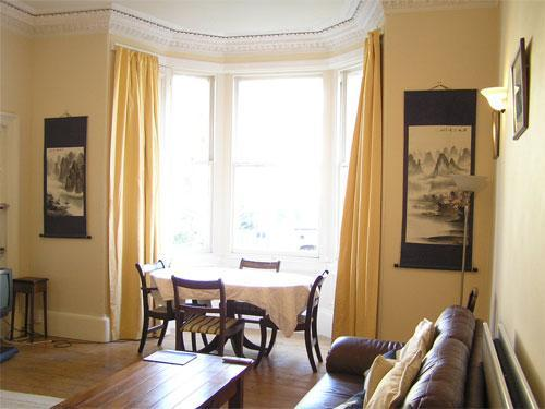 Living Room: gas fire in traditional fireplace, dining table, 2 sofas, bay window overlooking garden - Edinburgh: Gladstone Apt, Marchmont Self Catering - Edinburgh - rentals