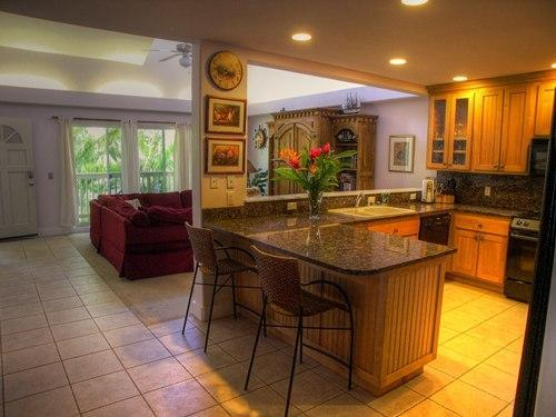 View from dining area through kitchen and living room - Moku Hale, Upscale 5 Bedroom Condo in Poipu - Poipu - rentals
