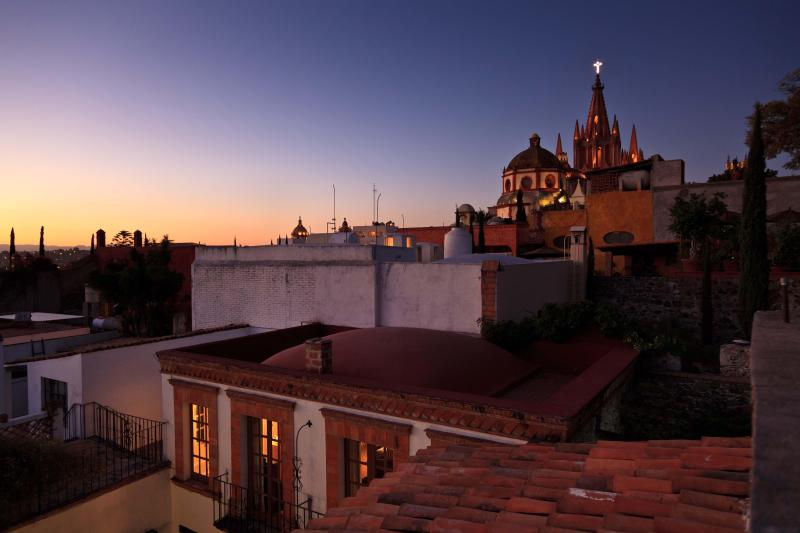 El mirador by evening, sprial staircase, view of lit windows of master bedroom, la Paroquia - Casa Piña SMA steps to Jardin, shadow of Parroquia - San Miguel de Allende - rentals