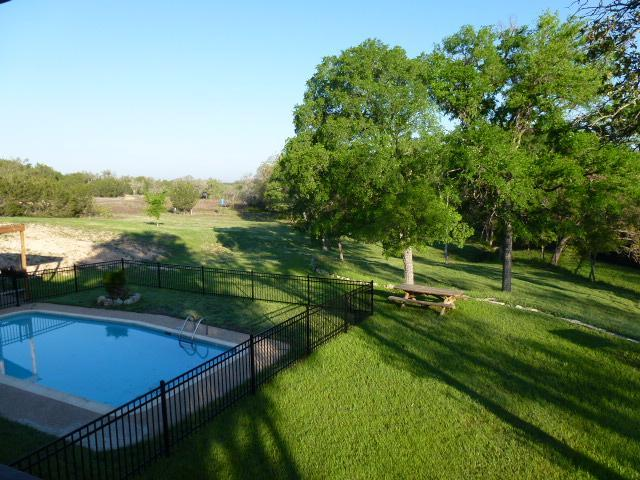 The back of our 3500 sq ft retreat looks out upon the refreshing pool and creek. - M&M Creekside Hill Country Retreat in Lampasas, Tx - Lampasas - rentals