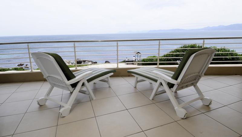 Balcony with gas barbecue and dining for six with ocean view across Walker Bay - 3-bed absolute seafront apartment in De Kelders - De Kelders - rentals