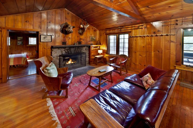 Living area with fabulous stone wood burning fireplace, Great vintage furniture - Creek Side Knotty Pine 1930s Lodge on 575 Acres - Milford - rentals