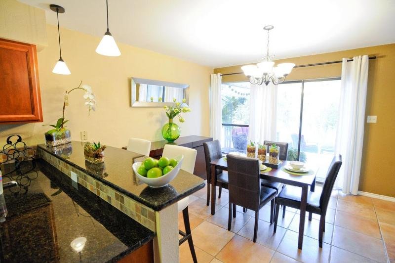 Kitchen with a raised bar, looking into the dining room, and then the patio door - Newly Remodeled Luxury Townhouse-Couples/Families - Austin - rentals