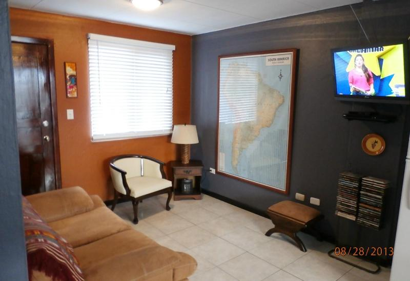 Living area with sofa, chair, flat-screen TV, DVR, stereo, and massive map of South America! - Right on El Centro's Doorstep!! - Cuenca - rentals