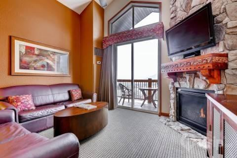 Spacious and comfortable living room with queen size sleeper sofa, stone fireplace, private balcony and 42