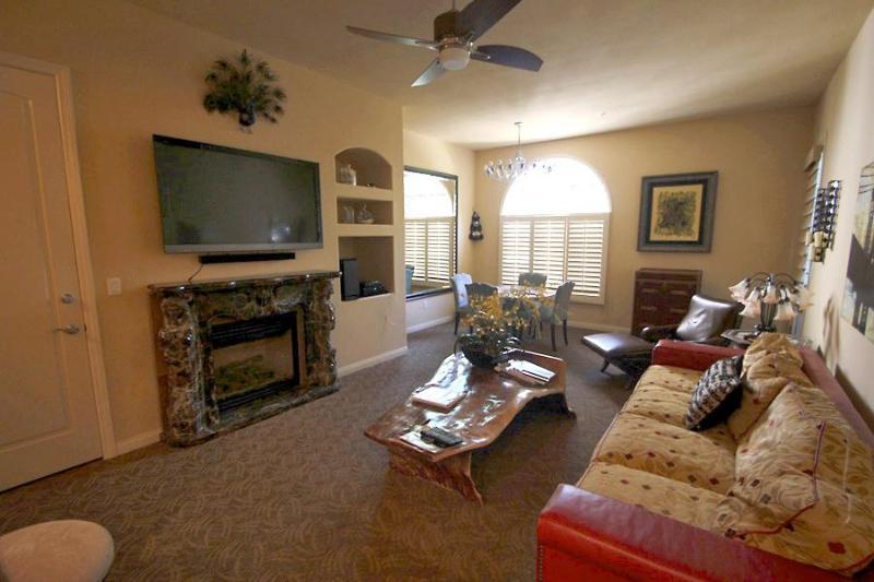 The living room has eclectic furniture. - Exquisite Ground-Floor Condo at Legacy - La Quinta - rentals