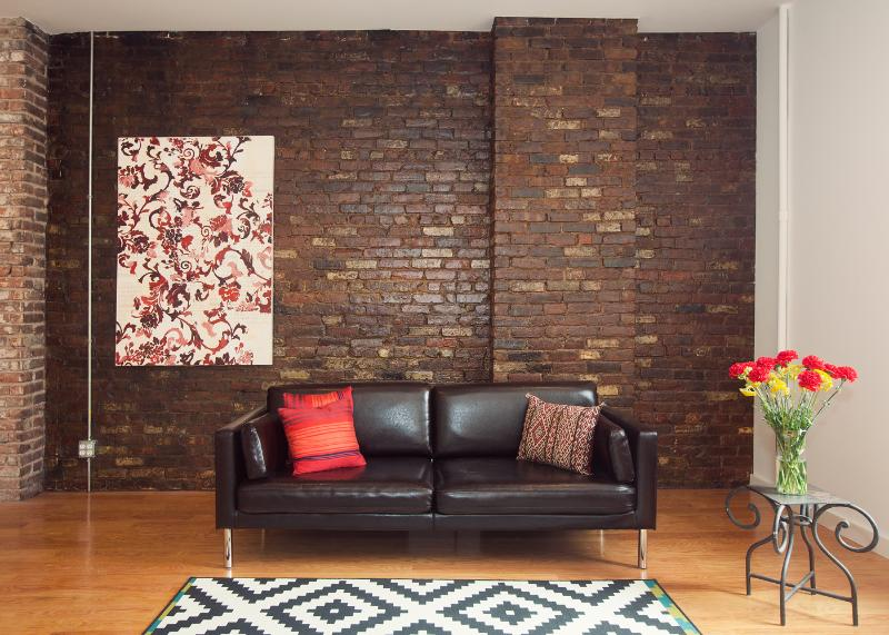 Exposed brick wall, original artwork, modern sofa in the living room - #1 by Lonely Planet -Creative Class-Luxury Loft - New York City - rentals