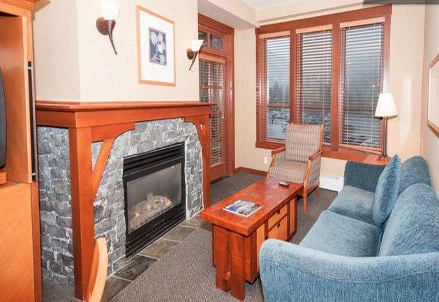 Living room with a stone hearth fireplace - Squaw Village Slopeside Condo Ski-in Ski-Out - Olympic Valley - rentals