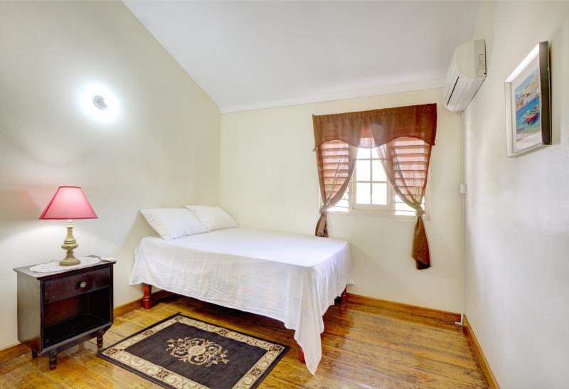 Warmly furnished master bedroom with double bed and A/C unit. - Gracie Homes 2 Bedrooms - Kingston - rentals