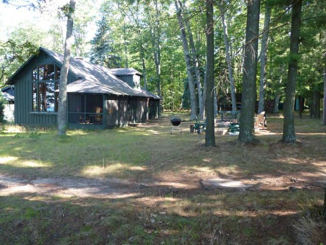 View from the entrance to the Deck, towards the cottage in a clearing, among tall trees. - Higgins Lakefront Cottage & dock, in Deep Woods - Higgins Lake - rentals