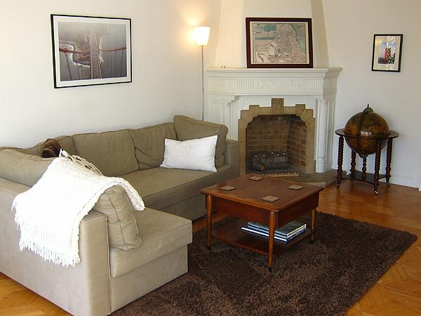 The spacious living room has a large sofa near the fireplace - Mid Century View Flat - Close to everything, Roomy & Bright, New Kitchen - San Francisco - rentals