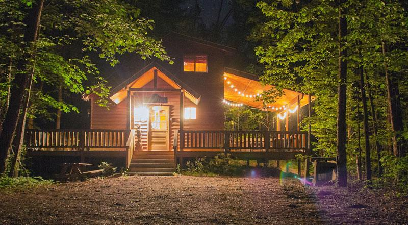 Night time view of The Bear Affair with outside living space and hot tub area lit up - The Bear Affair - Helen - rentals