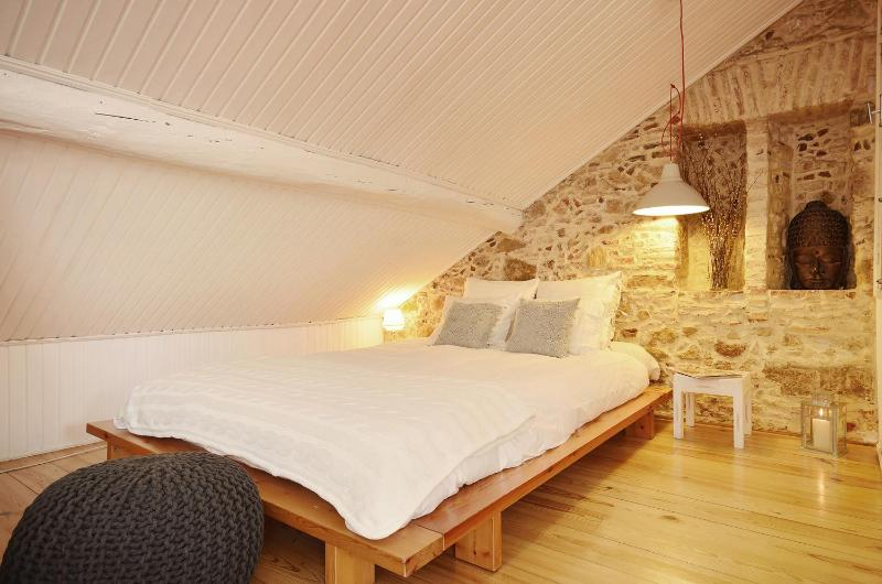 The large double bed sits against an original, stone wall adding a rustic and traditional feel - Romantic escape at downtown (Baixa/Chiado) - Lisbon - rentals