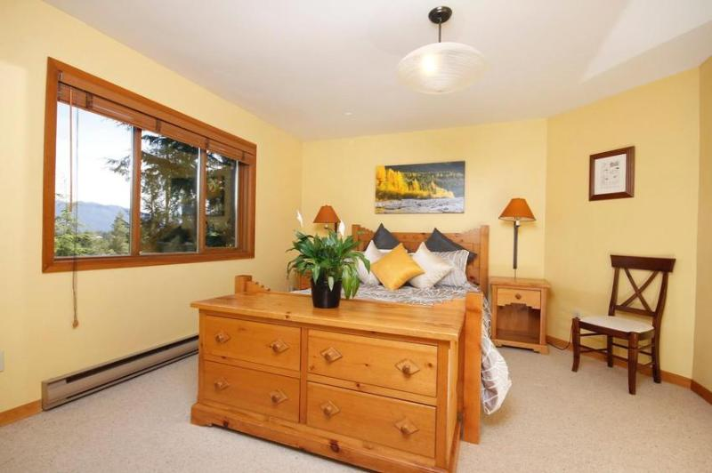 Bedroom 1 - A spacious, sunny bedroom with a queen bed, mirrored wardrobe and wooden dresser set. Has a full en-suite bathroom. Located on the top floor of the house, next to the kitchen. Art: Fall at Mamquam River - Aurora Lodge - Whistler - rentals