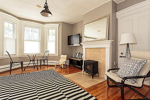 living room showing wood stove - Central JP 2 bdrm in Victorian near T - Jamaica Plain - rentals