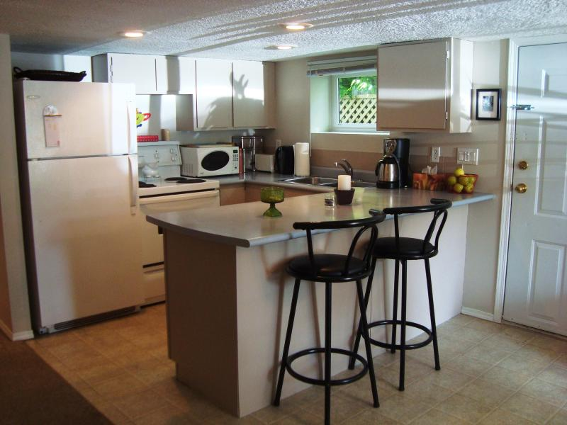 Kitchen, bar stools, and suite entrance - Bright, Comfortable, Perfectly Located, and Quiet Suite in the Heart of Victoria - Victoria - rentals