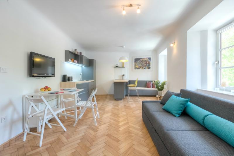 Spacious living room area with a big sofa, dining area and kitchen - 1-bedroom Študentovska - Fine Ljubljana Apartments - Ljubljana - rentals