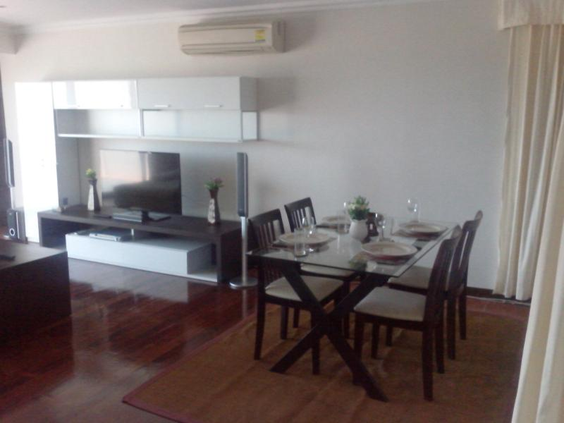 Living-dining room showing teak floor, dining table & entertainment area - Lovely, quiet Penthouse with sea views - Pattaya - rentals