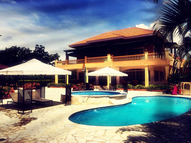 Back of lot view of the private pool, warm jacuzzi & poolside cabanas with house in the background - Luxury 6BR Dominican Golf Villa 5mins from beach - Juan Dolio - rentals