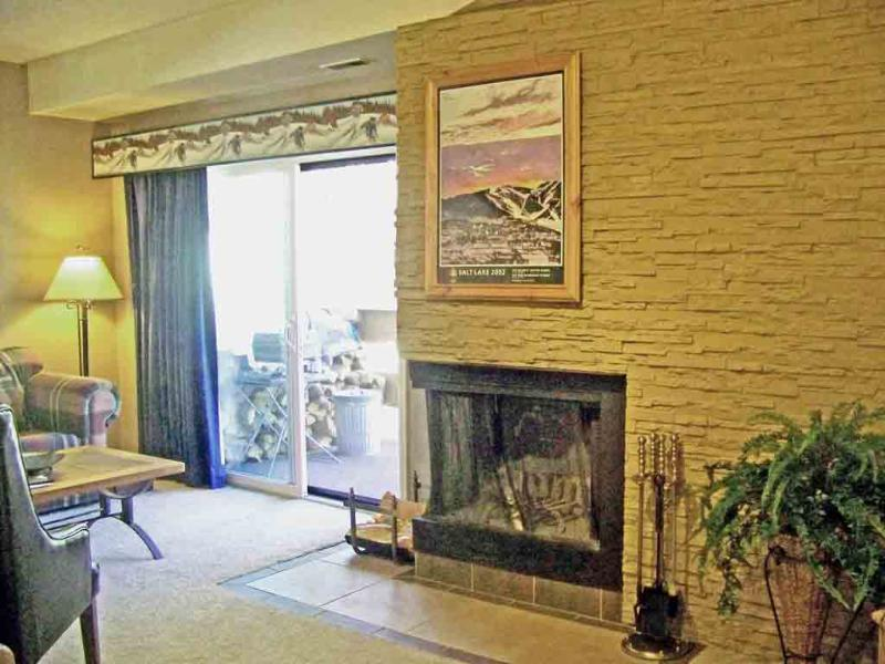 Living Room/wood burning fireplace set in stacked stone wall and glass door to deck - Lift Line 207 Walk to PCMR - Many Sundance Venues - Park City - rentals