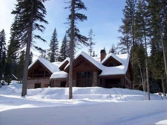 Tall Ponderosa Pines frame this custom home with lake views - The Rock House - 3 Bedroom, 4.5 baths, Sauna. Private office area. Custom home sleeps 10-12. WIFI - Tamarack Resort - rentals