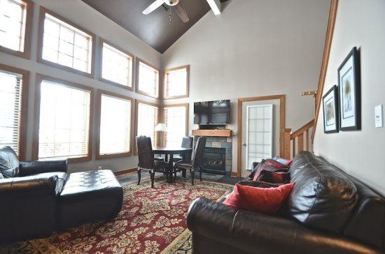 Spacious Living Room with Queen Sofa Sleeper, Fireplace, Ski Hill Views from the Wall of Windows, and Vaulted Ceilings - 3BR Disciples Village Ski In/Ski Out Condo - Slopeside on Boyneland Run, Completely Remodeled, Sleeps 12 - Boyne Falls - rentals