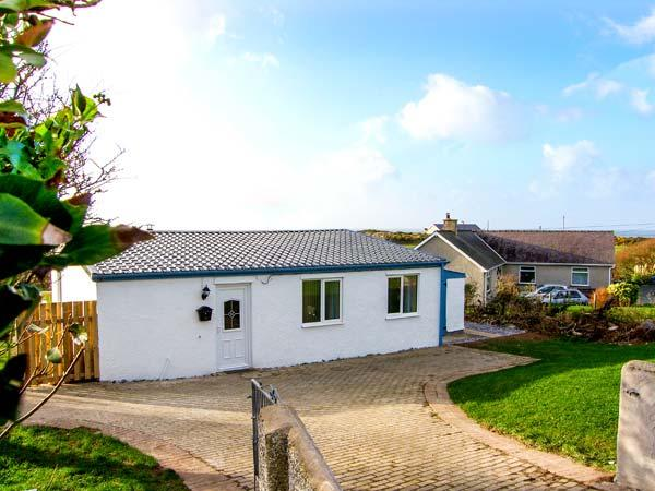HARBOUR LIGHTS, detached, ground floor cottage, 5 mins walk from beach, woodburning stove, hot tub and sauna, in Church Bay, Ref 916899 - Image 1 - Church Bay - rentals