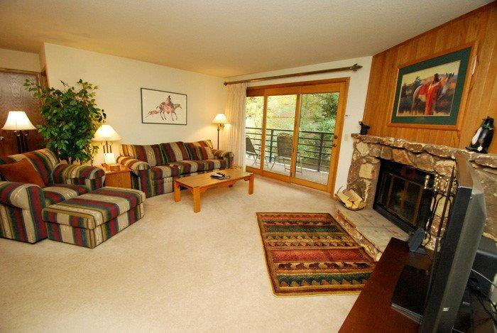 Spacious living room opening to an outdoor balcony  - Snowdance Manor 205 - Walk to slopes, indoor pool and hot tub, Mountain House! - Keystone - rentals