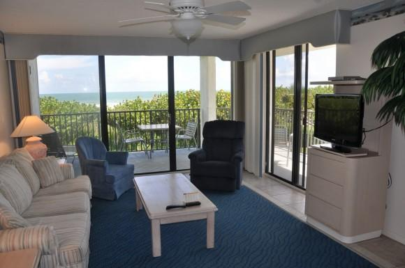 Living room loaded with comfy furniture, flat screen TV, and a wrap-around balcony. This is a southeast 2nd floor corner unit. - Beach Condo Rental 208 - Cape Canaveral - rentals