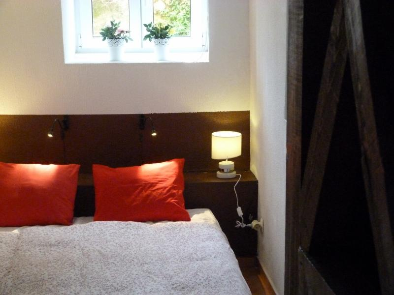 Bedroom with glimpse of antique wooden structure - MOURARIA III, historic duplex in Lisbon centre - Lisbon - rentals