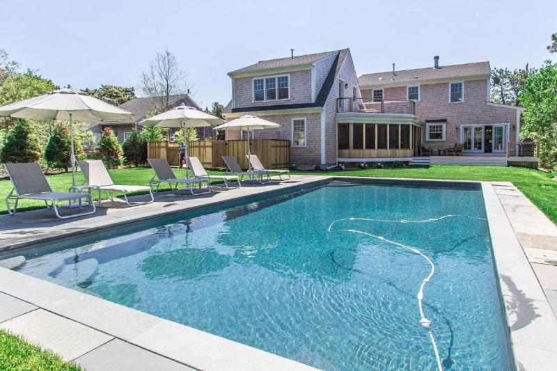 Pool, Patio, and Yard side of House - MANNB -  Designer Home with 18 x 30 Heated Pool,   Spacious Deck and Screened Porch-Outdoor dining for 12. Nicely located 1 mile to South Beach and 1.5 miles to Edgartown Village Area. - United States - rentals