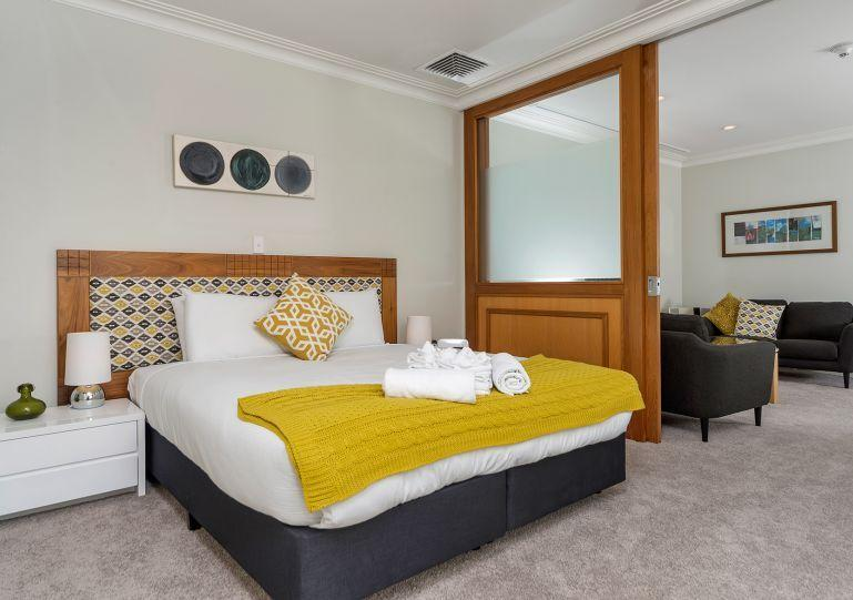 Large slider door opens bedroom into the living room - One Bedroom Serviced Apartment in the Heritage Towers, Auckland - Auckland - rentals