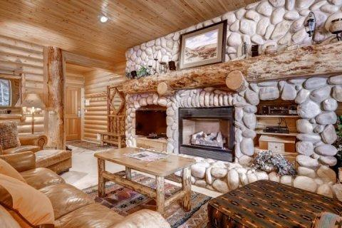 Rustic mountain interior with custom leather furnishings, hand crafted floor to ceiling creek stone fireplace, 42