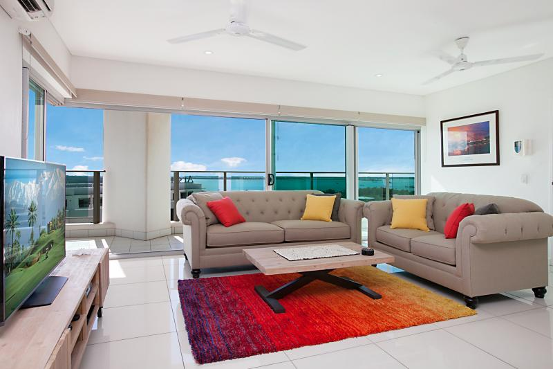 Lounge with wide sliding doors opening to the balcony, view and sea breezes - Beachlife Sea Breeze - Stunning Harbour Views 3BRM - Darwin - rentals