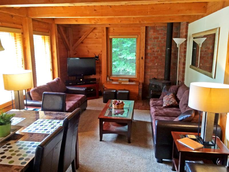 Left Unit: Cozy living and dining room with a wood burning stove and firewood. - The Cabin at Killington: Left Unit - Killington - rentals