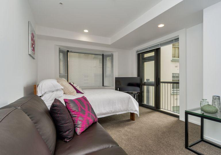 Open plan living area with large comfortable couch - Large studio apartment in central Auckland with views of the CBD - Auckland - rentals