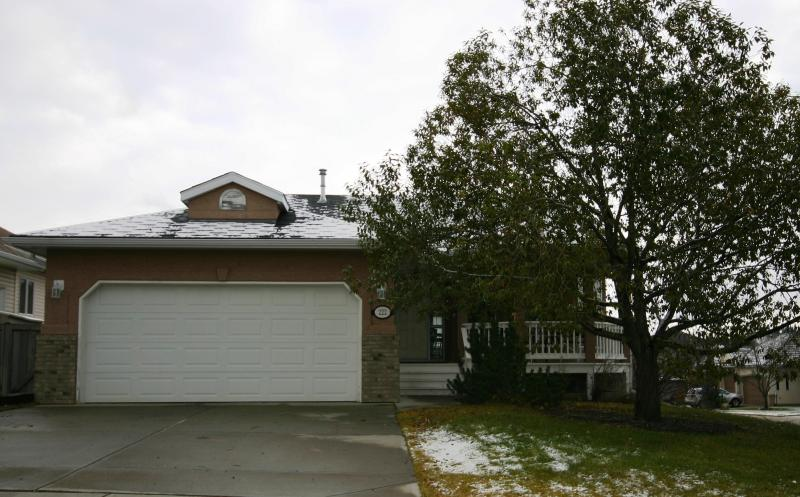 Front exterior of home, includes double attached garage with remote opener. - West Terrace Bungalow - 4 bedrooms, Cochrane, AB - Cochrane - rentals