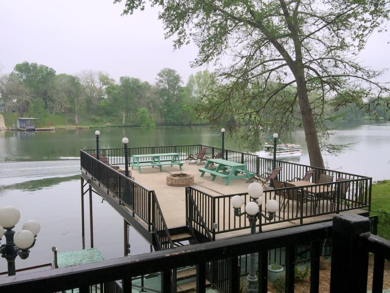 Scenic view from the cottage balcony of upper deck and boaters on the river - GUADALUPE RIVER LODGE-NEW BRAUNFELS-HILL COUNTRY - New Braunfels - rentals
