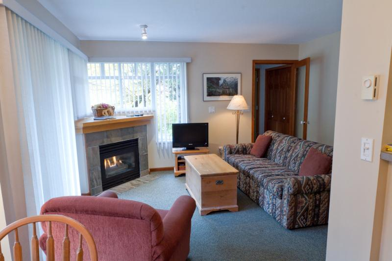 A cozy living room with gas fireplace, flat screen tv and adjacent patio. - Sunpath 46 1 bdrm, pet-friendly condo in Whistler - Whistler - rentals