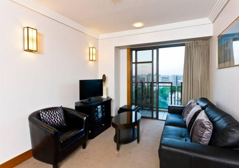 Sunny lounge opens out onto balcony - Two bedroom apartment in Metropolis Residences - Auckland - rentals