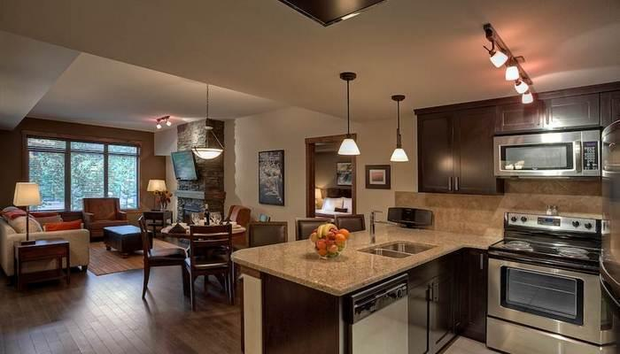 This chic condo features a sleek kitchen with high-end appliances and a breakfast bar. - Canmore Stoneridge Luxury 2 Bedroom Family Condo with Pool and Hot Tub - Canmore - rentals