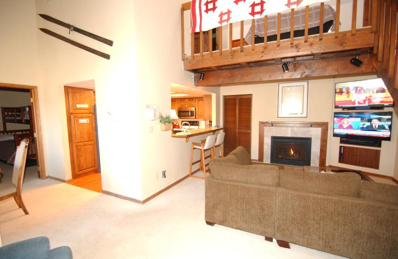 Entry area showing living room with natural gas fireplace,  large couch, Dual TV entertainment wall. - Brian Head Penthouse North, Pool, Ski-i/o Sleep 16 - Brian Head - rentals