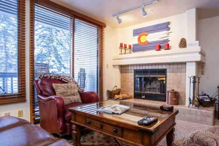 Living room with wood burning fireplace and deck access with seating for 2. - Townsend Place Condo, Walk to Beaver Creek Village, Ski In/Ski Out, YR Hot Tub, Convenient Location! - Beaver Creek - rentals