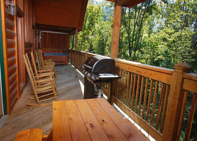 Deck with picnic table, grill, porch rockers and hot tub. - Enclosed Resort Pool, Theater Room, Picnic Table, Pool Table - Pigeon Forge - rentals