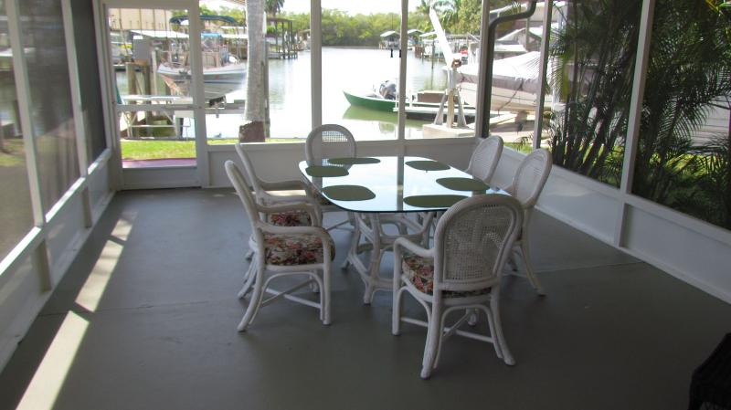 Patio area looking down long canal and boat dock area. - Prime Fishing - Island Retreat Where Dolphins Play - Saint James City - rentals