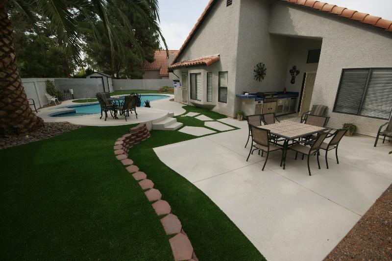 large dining area & outdoor kitchen, smaller table near pool & spa. - spa! pool! , PITCH & PUTT in yard,  GOLF Course - Henderson - rentals